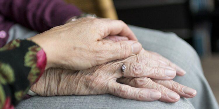 Mani di anziani che si stringono