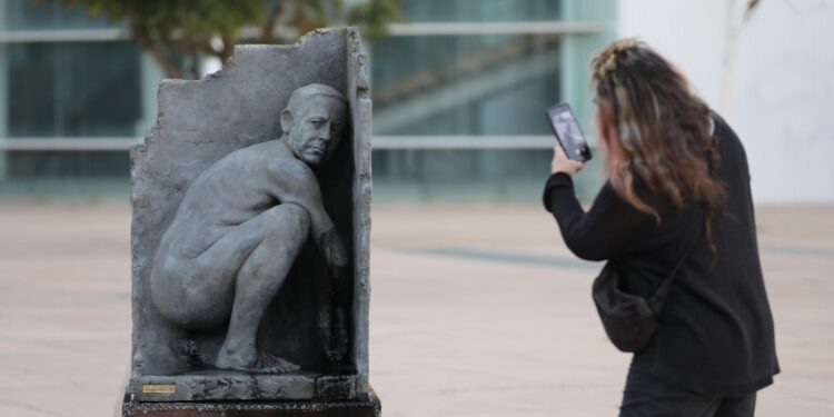 Il premier rappresentato nudo e accovacciato