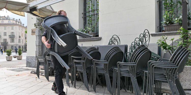 Un barista ripone delle sedie a causa delle chiusure