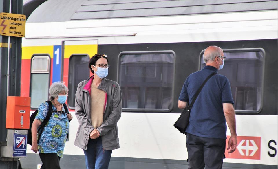 Persone con mascherina in attesa del treno