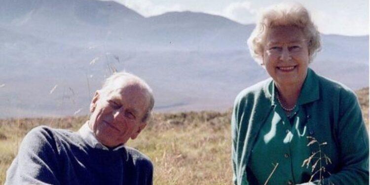 Elisabetta e il consorte seduti su un prato in Scozia