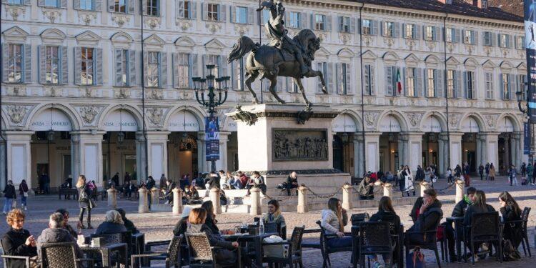 File fuori dai negozi e caffè sulle panchine di piazza San Carlo