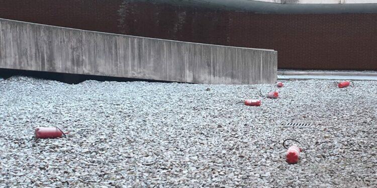 Degli estintori a terra sull'asfalto davanti all'autosilo Valmulini