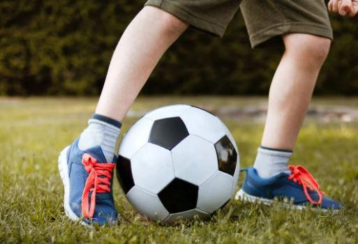 Palla da calcio tra i piedi di un bambino