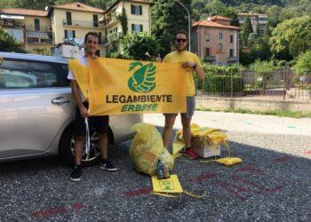 i rappresentanti della Legambiente erbese con in mano la loro bandiera e un sacco dell'immondizia