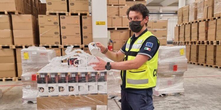 un uomo dell'agenzia delle dogane con una tazza contraffatta e i pacchi della spedizione
