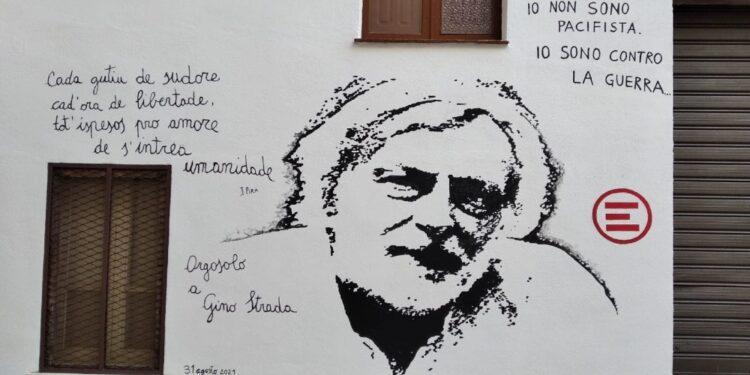 Il viso stilizzato e le frasi celebri su un muro in centro